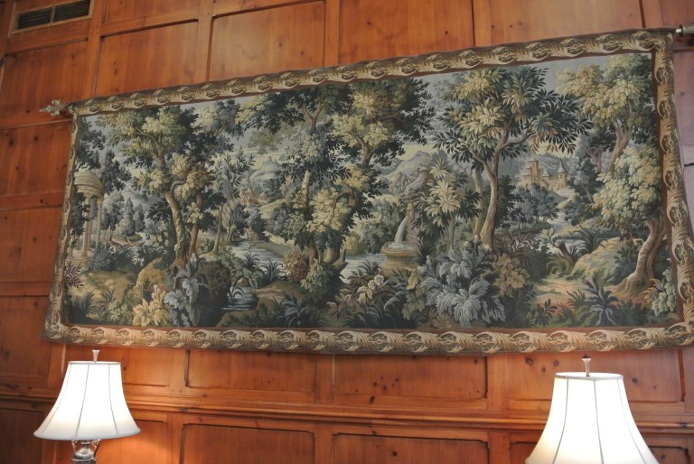 A tapestry on a wood paneled wall at the O'Henry Hotel.