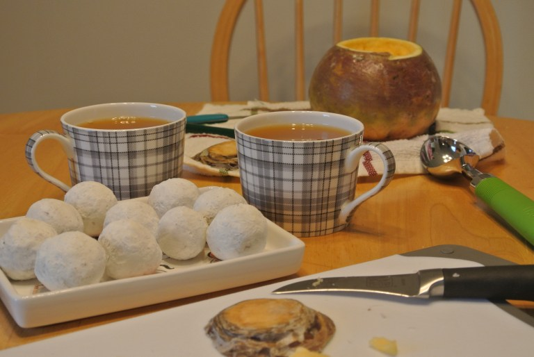 A plate full of powdered doughnuts, two mugs of tea, and a carved turnip.