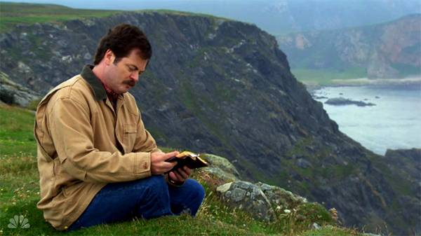 Ron Swanson from Parks and Rec sitting on a cliff reading a poem.