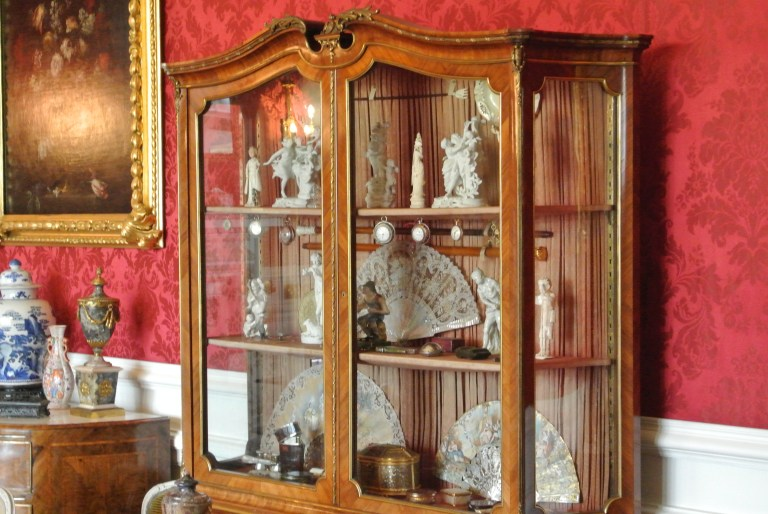 A brown cabinet with antique fans and figurines.
