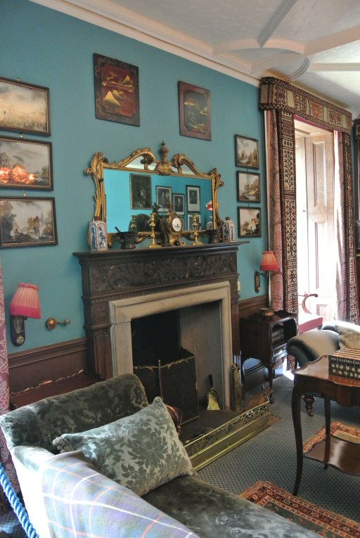 A blue sitting room with a fireplace and antiques.