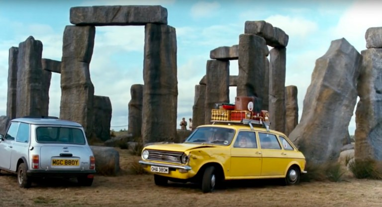 A silver and yellow car parked in front of Stonehenge.