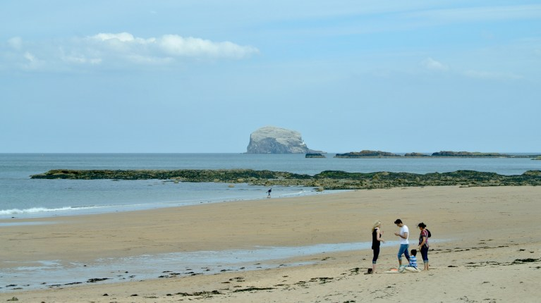 Three adults and a child on a brown sandy beach in front of Bass Rock in the Firth of Forth.
