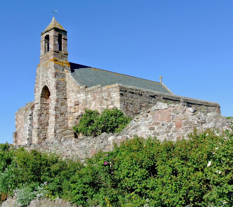 A stone church against green shrubbery and a bright blue sky.