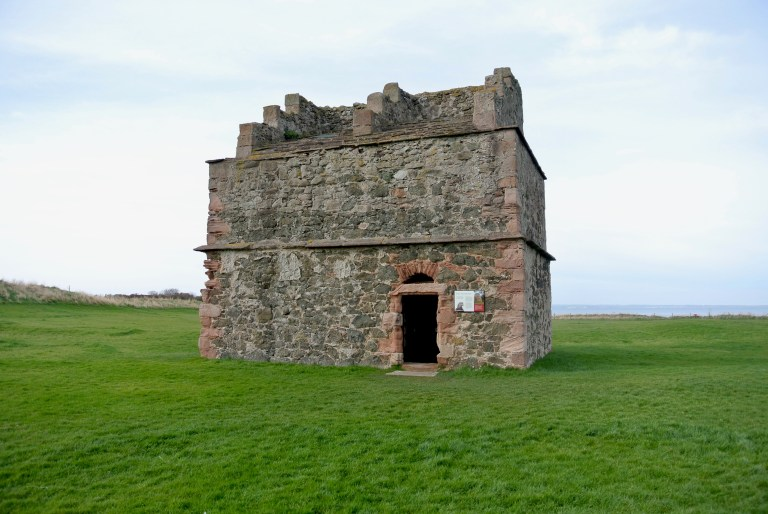A doocot from the 1600s in a green field.
