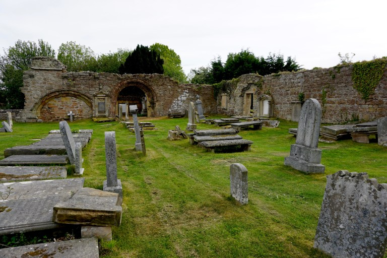 Kinloss Abbey ruins and old falling down gravestones.