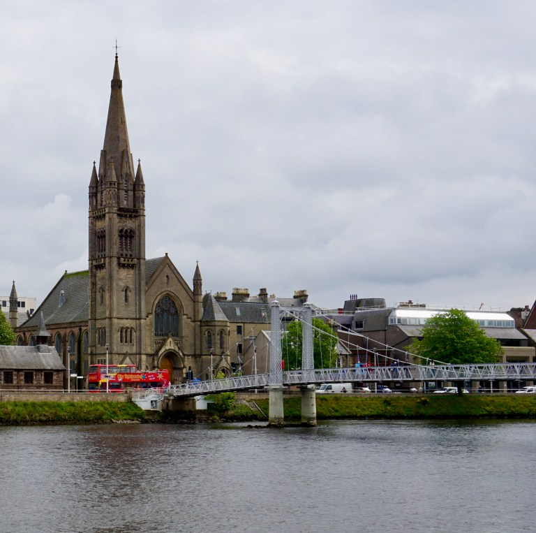 In Inverness, Scotland-a church with a tall spire, a red double decker bus, and a foot bridge crossing over a river.