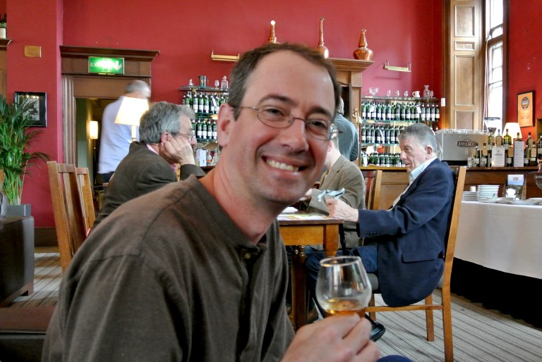 A man holding a glass of whisky and smiling.