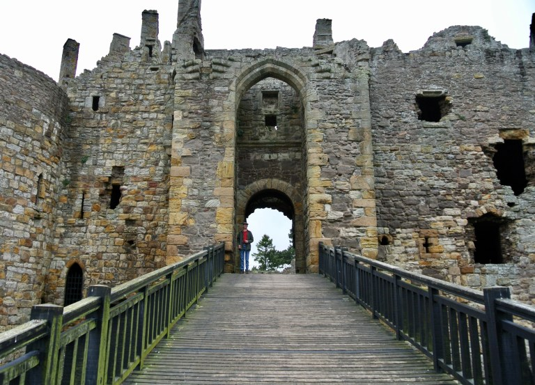 A man standing at the end of a wooden bridge, in the doorway of Dirleton Castle.