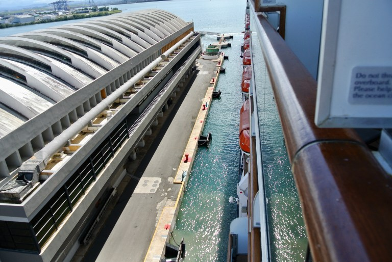 A very narrow strip of blue water between a cruise ship and the cement walkway that it is pulling up next to.