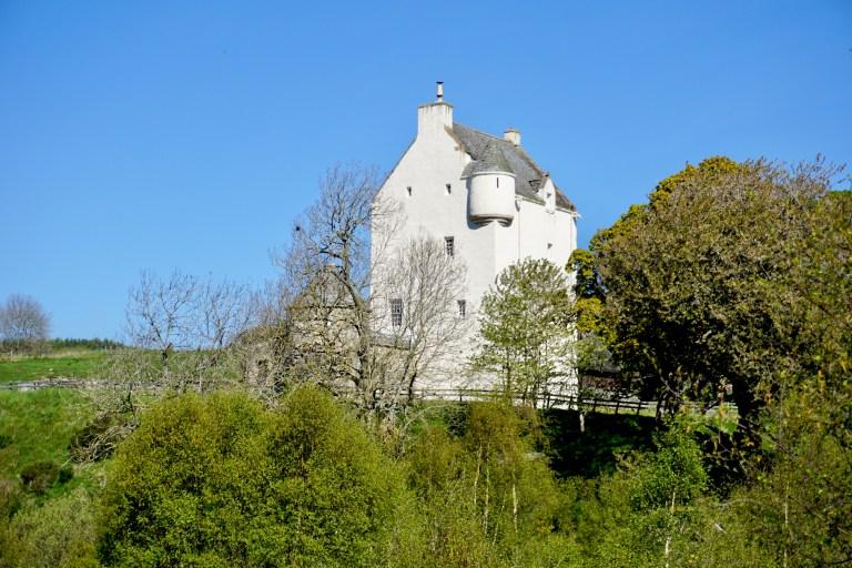 Muckrach Castle under a bright blue sky.