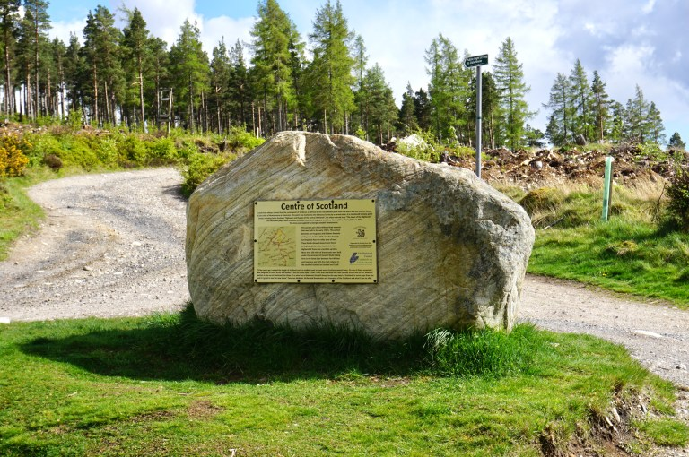 A large boulder with the Centre of Scotland sign tacked onto it.