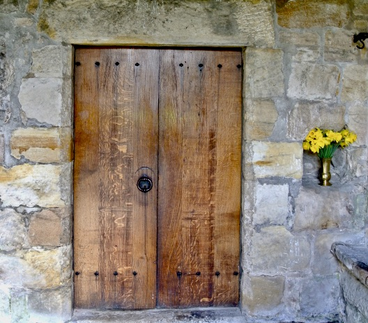 A vase with yellow flowers next to large wooden doors of a church.