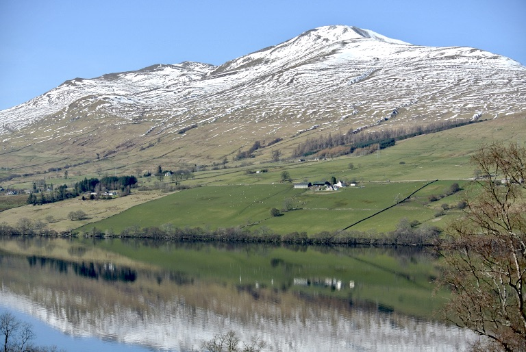 Snow covered hills and green grass reflected in water.