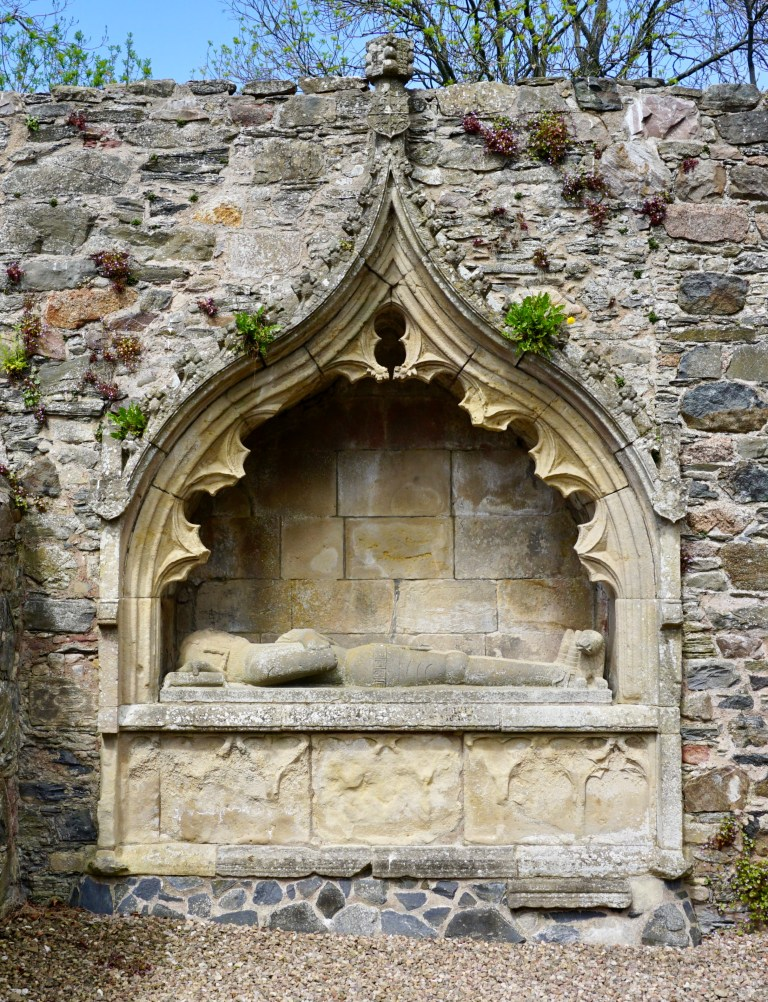 A stone effigy  of a knight on a tomb.