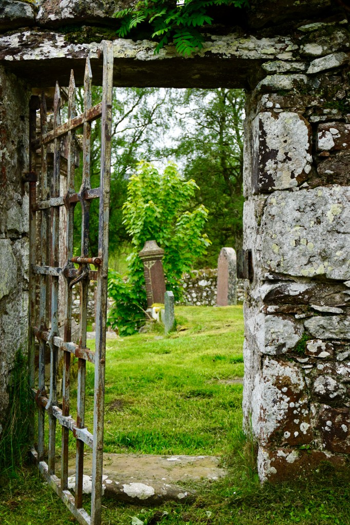 A stone doorway and a rusty iron gate at Dunlichity Church and Cemetery.