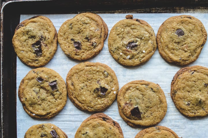 Baked chocolate chip cookies on a baking sheet with parchment paper