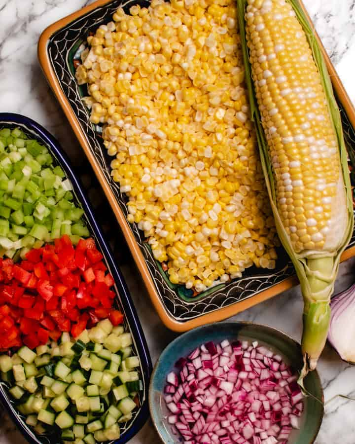 Prepared vegetables for corn salad plus one whole ear of corn
