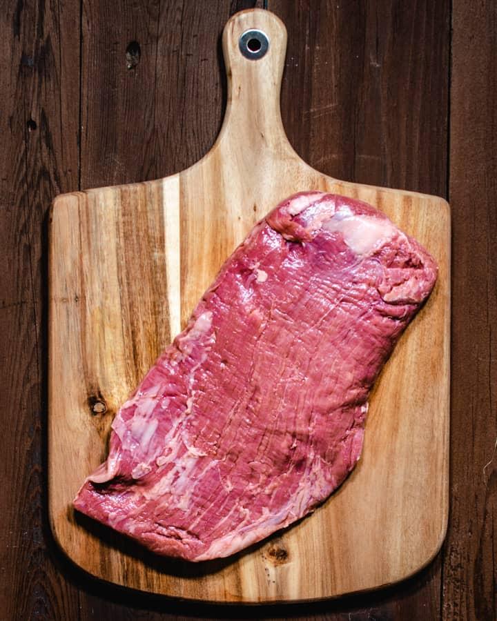 flank steak before marinating on a cutting board