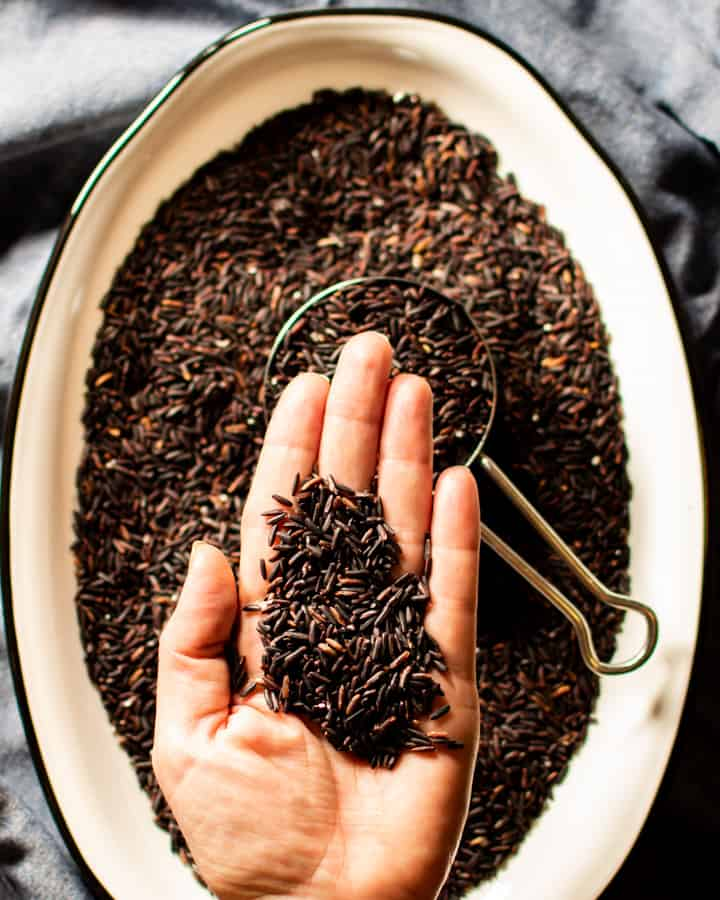 raw black rice in palm of hand over white dish