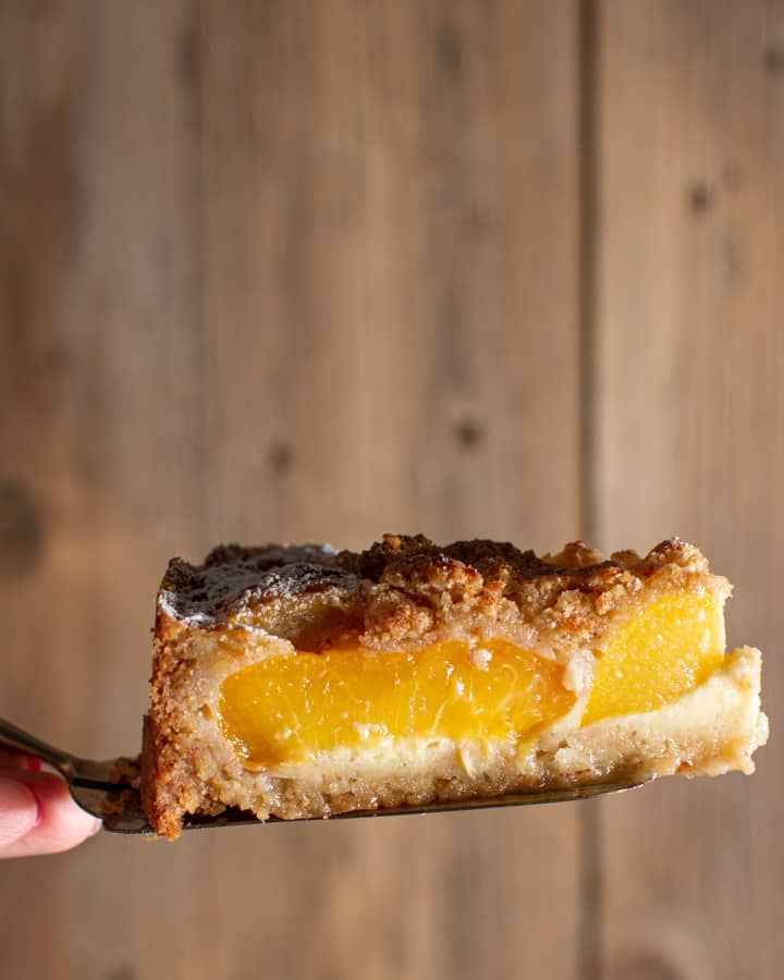 close up of a slice of peach and almond tart