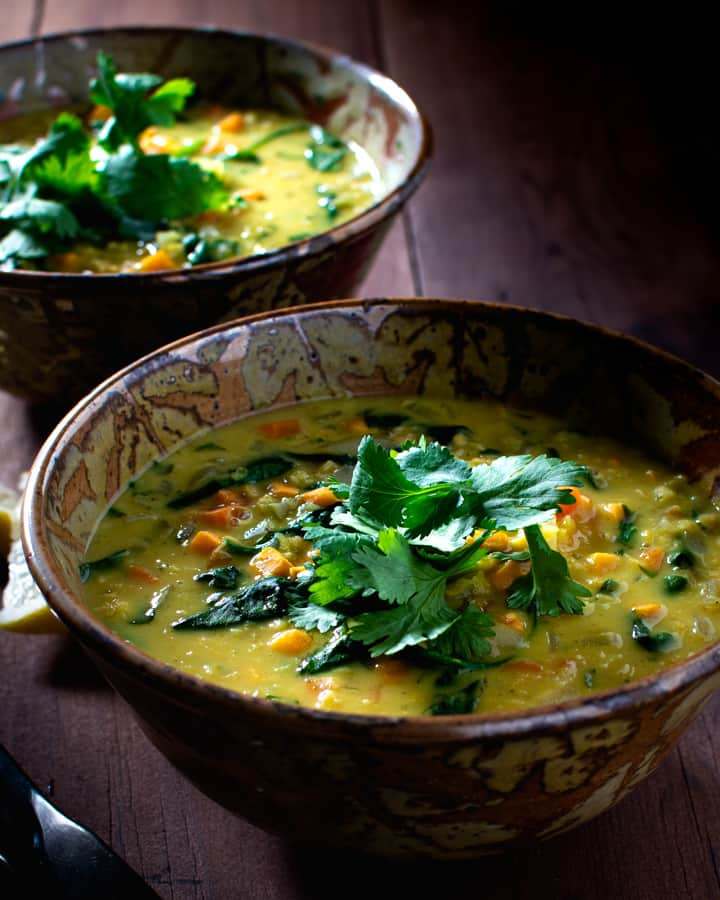 two bowls of red lentil and vegetable soup garnished with cilantro