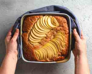 baked apple caramel pudding cake held in hands
