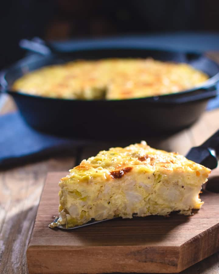 slice of cauliflower frittata on wood board with cast iron pan in background