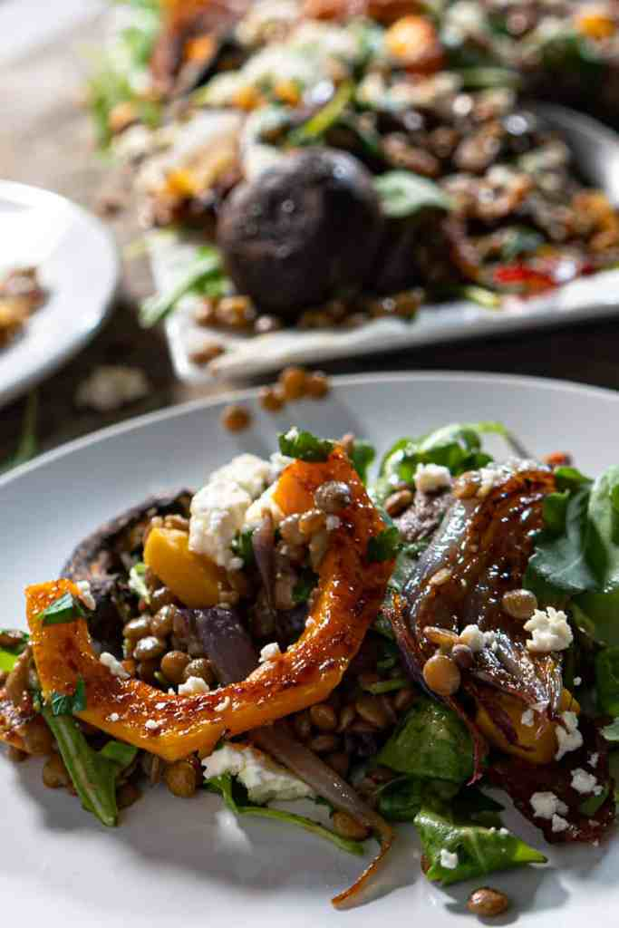 close up of single serving of warm lentil salad with roasted vegetables and bacon