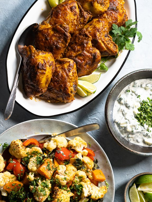 Curried chicken, vegetables and Cucumber Raita in seperate dishes on blue background