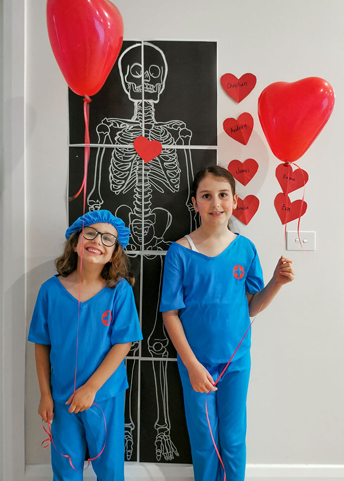 Kids Doctor themed birthday party - Girls dressed in surgical scrubs atanding in front of skeleton poster