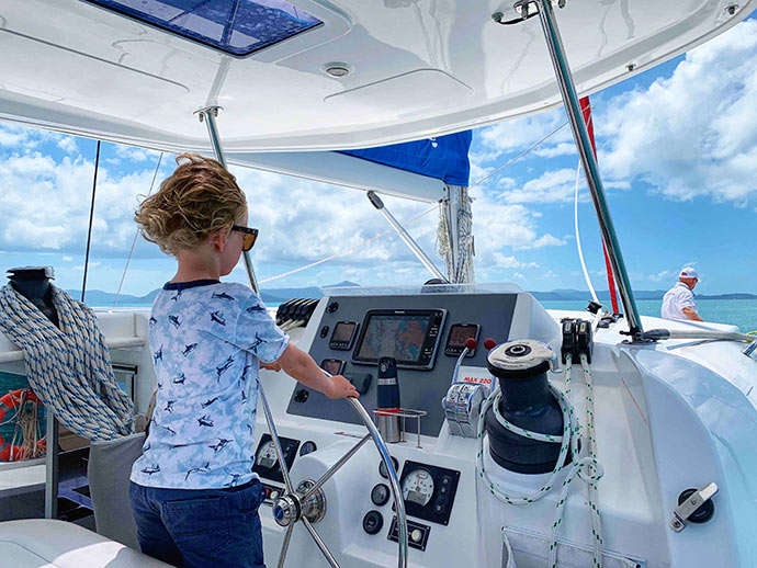 charter a yacht on airlie beach - child at helm of yacht