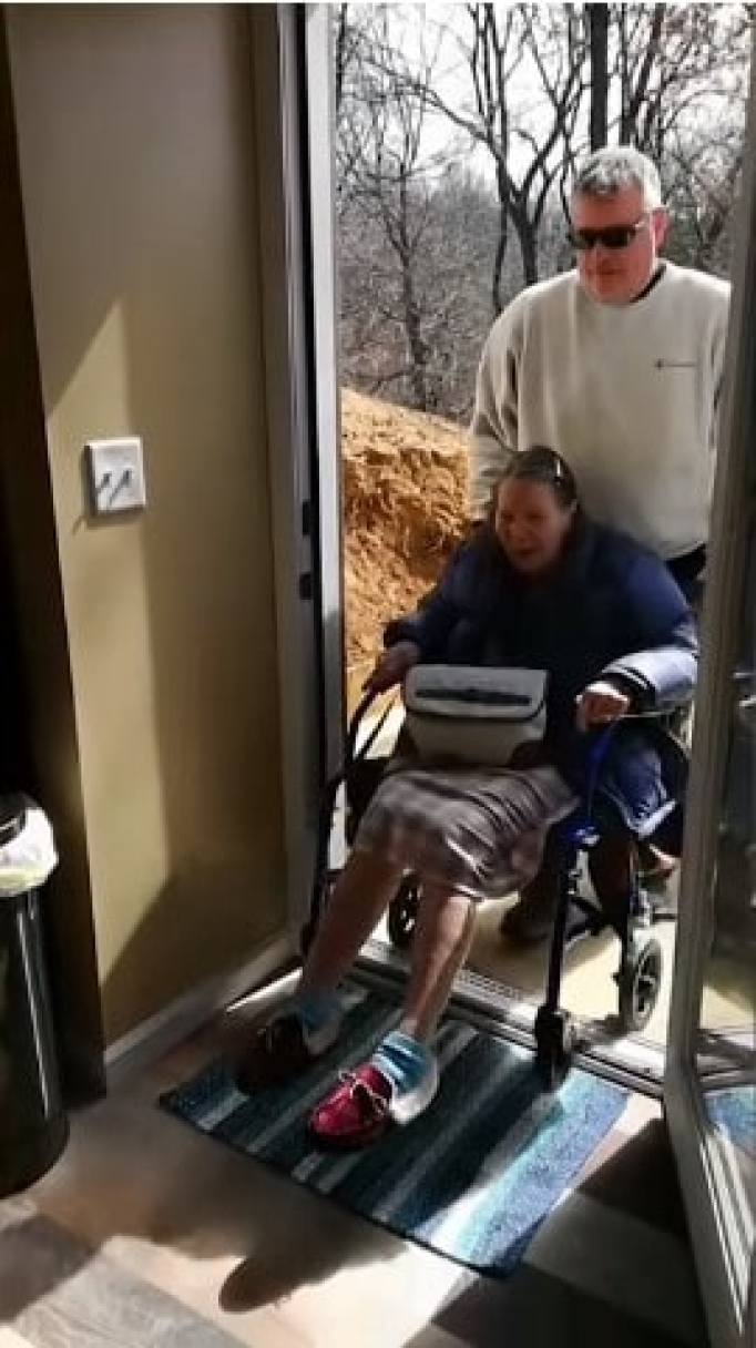 Bonnie Miller being wheeled into their new custom mini home