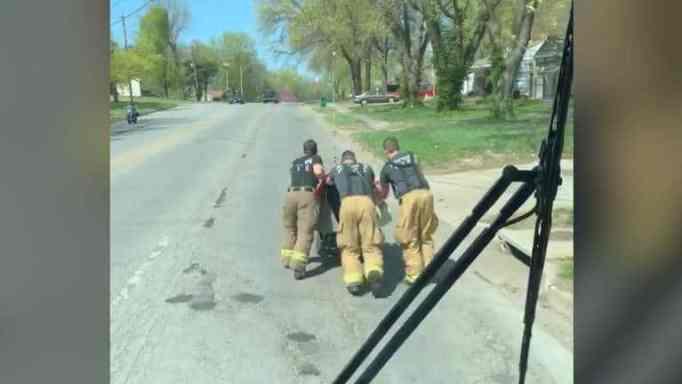 Firemen pushing the elderly veteran's wheelchair