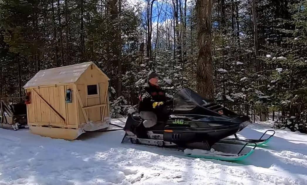 Man dragging along his snowmobile camper