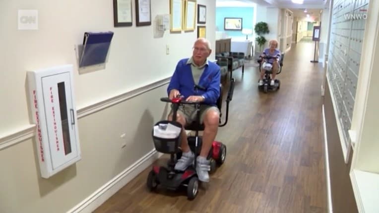old couple riding scooters