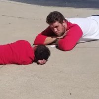 Assistant principal lays down on the ground to help student with autism feel better