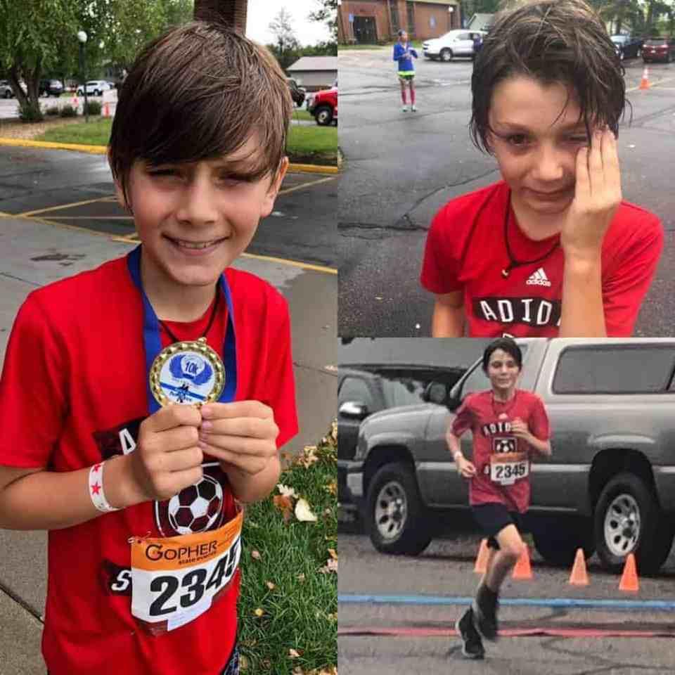 Kade holds medal for 10K race.