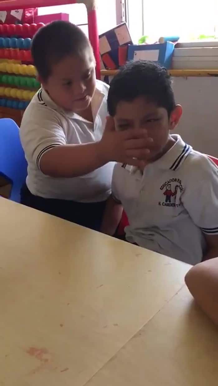 Boy with down syndrome comforts classmate in an elementary school.