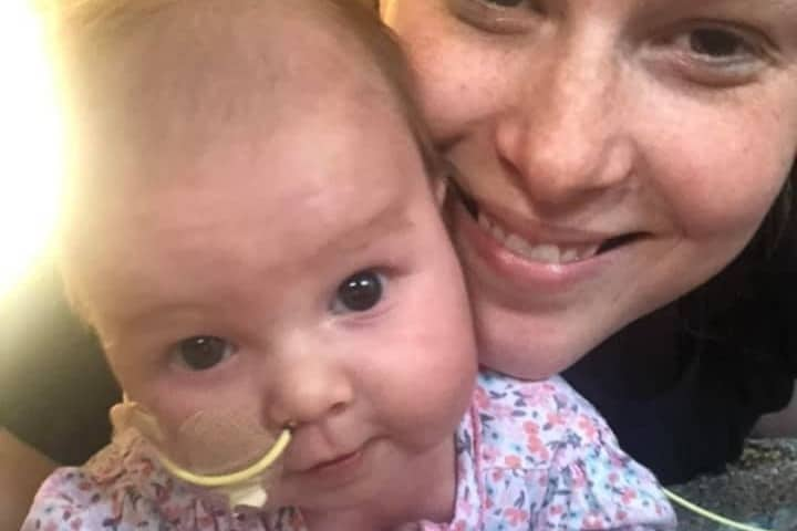 Beaming mom of neonatal intensive care unit baby who survived cancer.