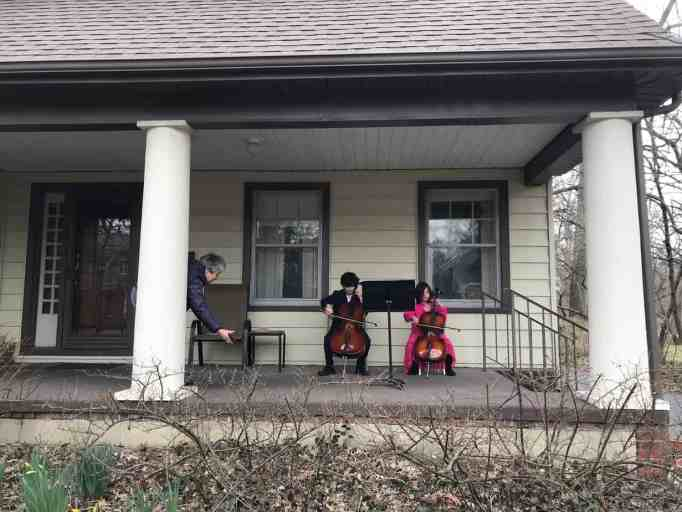 Two siblings playing cello instrument for elderly neighbor