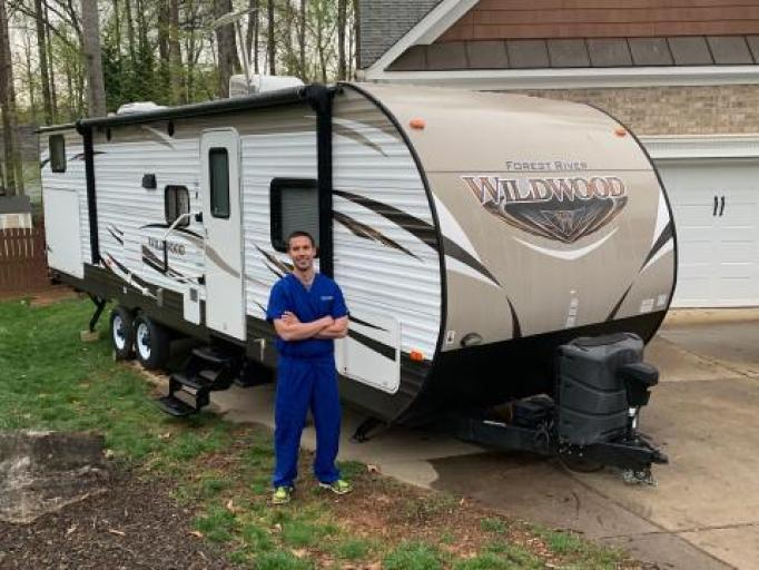 Healthcare worker standing in front of an RV.