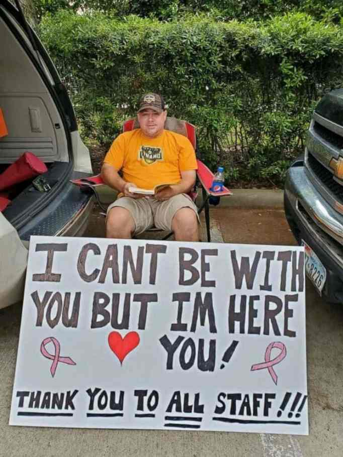 Husband waits with a sign for wife getting chemo at a cancer center.