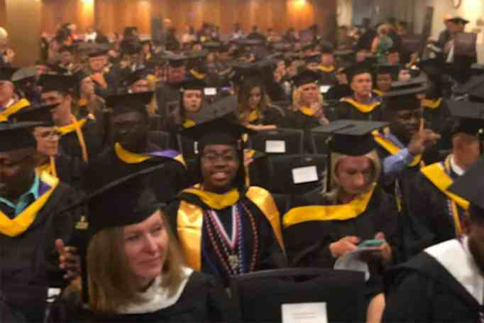 Teenager graduates with a master's degree.