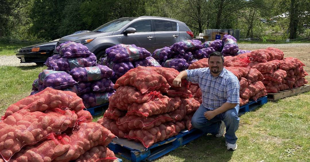George Ahern posing with bags of potatoes and onions for distribution to food banks