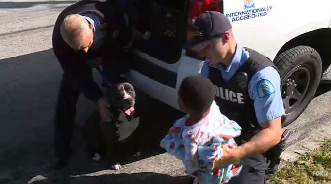 Police officers with Kh'amorion Taylor and the pit bull who guarded him