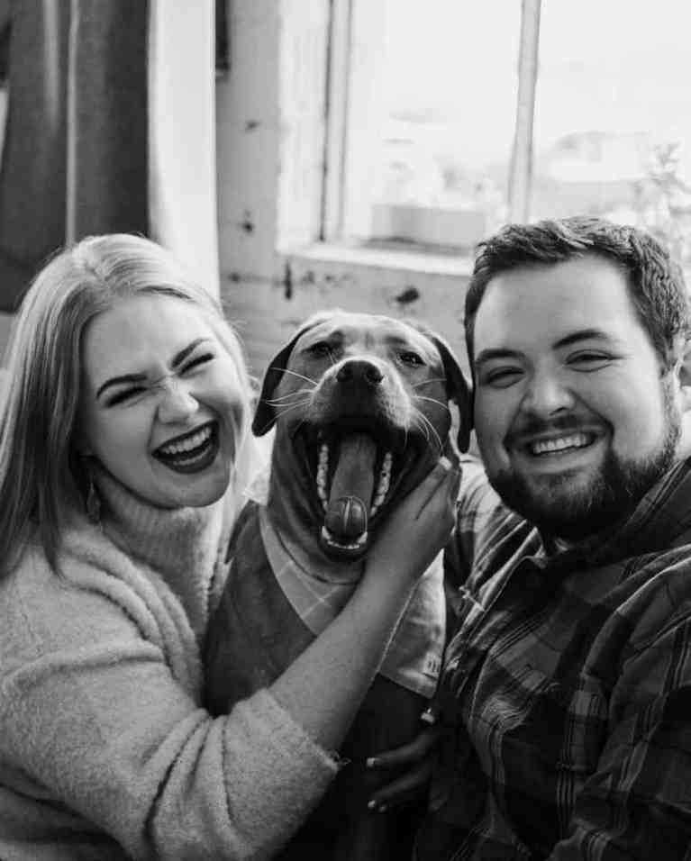 The couple posing for a picture with their beloved pet in the middle.