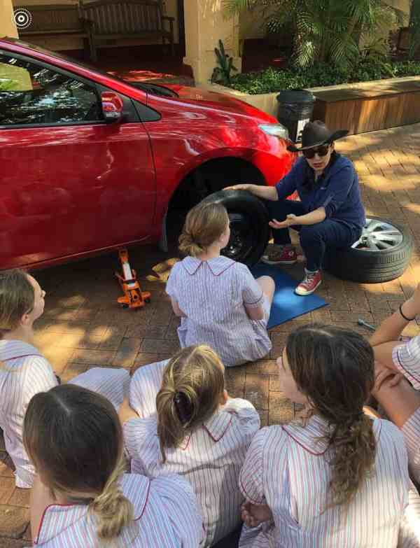 A woman teaching a group of teenage girls basic car maintenance