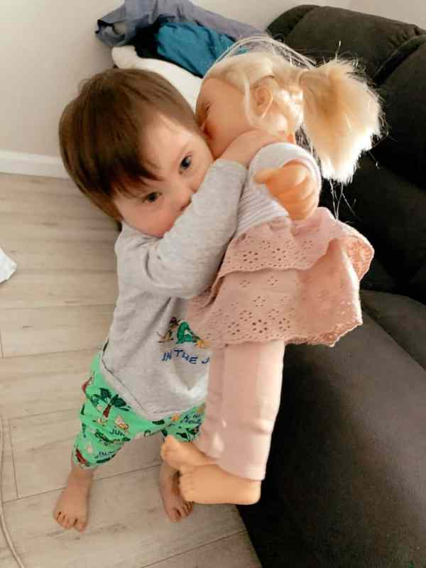 Elijah playing with a doll with Down syndrome