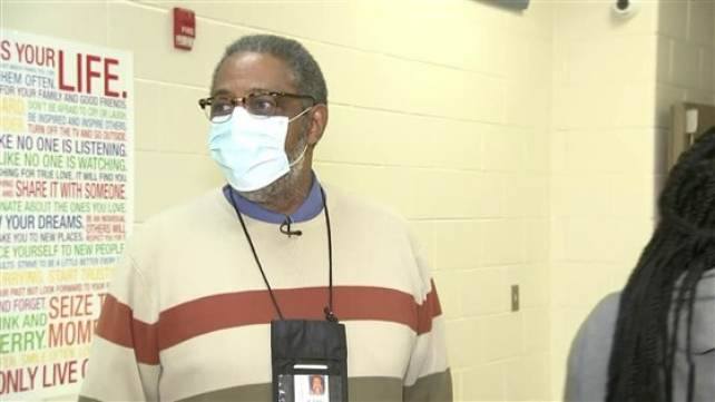 A principal wearing a face mask and standing at the school hallway